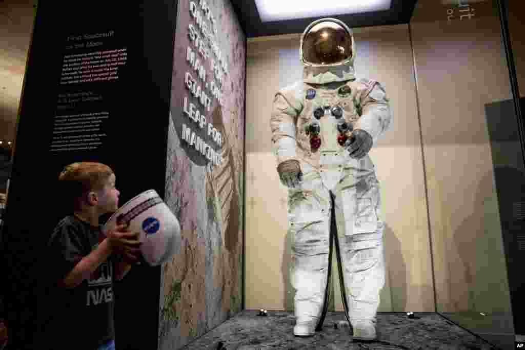 کودکی پنج ساله به لباس فضانوردان آمریکایی که پنجاه سال پیش پا روی ماه گذاشتند، می نگرد.