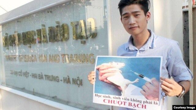 """Nguyễn Thành Nhân cầm tấm biển: """"Học sinh, sinh viên, không phải là chuột bạch"""" trước cổng Bộ Giáo dục và Đào tạo."""