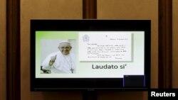 """ផ្ទាំងទូរទស្សន៍បង្ហាញពីលិខិតចេញផ្សាយថ្មីរបស់សម្តេចសង្ឃប៉ាបហ្រ្វង់ស៊ីស ចំណងជើង """"Laudato Si (Be Praised), On the Care of Our Common Home"""" នៅក្នុងសនិ្នសីទមួយក្នុងបុរីវ៉ាទីកង់ កាលពីថ្ងៃទី១៨ ខែមិថុនា ឆ្នាំ២០១៥។"""