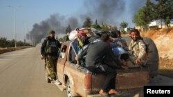 지난달 30일 시리아 반군이 알레포 서부 다히예트 알-아사드 지역에서 피난민들을 픽업 트럭에 태우고 퇴각하고 있다.