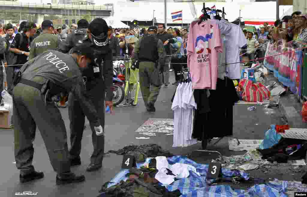 Police officers investigate the scene where an explosion took place near a camp of anti-government protesters at the Victory Monument, Bangkok, Thailand, Jan. 19, 2014.