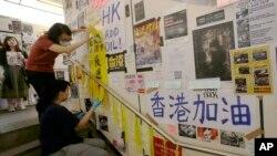 在台灣的香港學生為執行當地政府的指令從一面連儂牆上移走標語。(2019年8月31日)