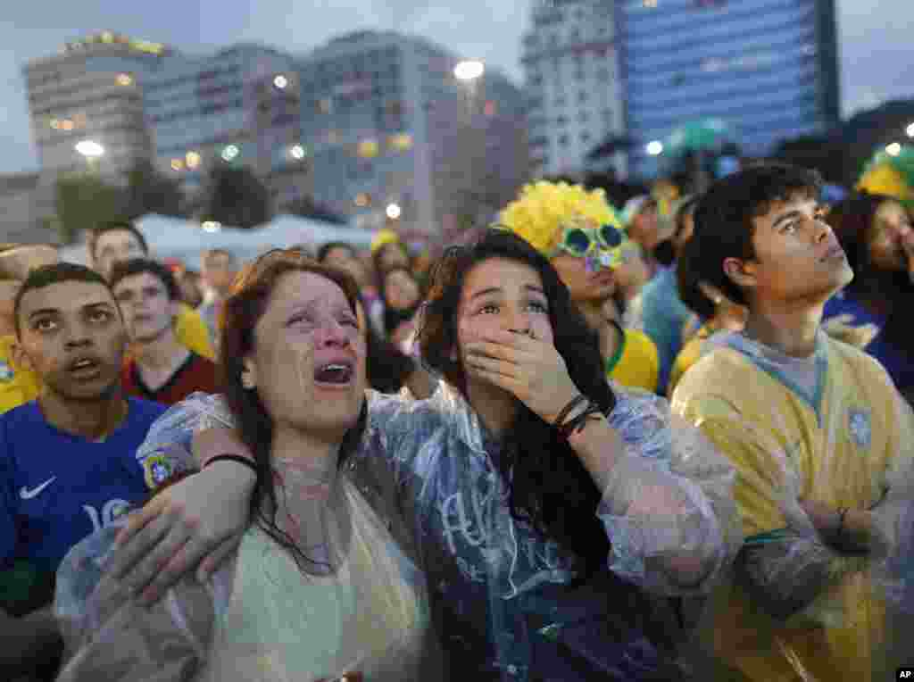 Brazil soccer fans cry as they watch their team lose 7-1 to Germany at a World Cup semifinal match on a live telecast inside the FIFA Fan Fest area on Copacabana beach in Rio de Janeiro, Brazil, July 8, 2014.