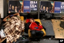 FILE - Homeless people rest downtown in Buenos Aires, Argentina, Oct. 21, 2015.
