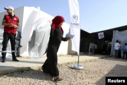 A Syrian refugee carries a bag she received as aid for the winter from the United Nations refugee agency (UNHCR) in Tripoli, northern Lebanon, Nov. 18, 2015.
