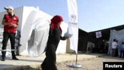 Seorang pengungsi Suriah menerima bantuan dari UNHCR di Tripoli, Lebanon utara, 18 November 2015. (Foto: dok.)