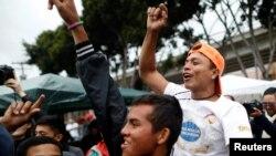 Migrantes centroamericanos de una caravana que llegó a la frontera entre México y Estados Unidos; saludan la noticia de la primera persona que logró ingresar a territorio estadounidense para pedir asilo. Lunes 30 de abril de 2018.