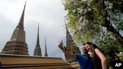 Western tourists snap a souvenir photo at a Wat Pho temple in Bangkok, Thailand.