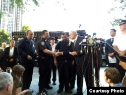 New York City Police Commissioner Bill Bratton greets Sgt. Hameed Armani, right, and Officer Peter Cybulski at a news conference at Columbus Circle in New York, July 21, 2016.