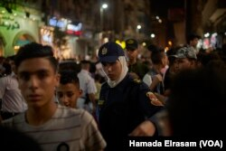 FILE - Policewomen show up on duty at movie theaters to organize crowds and protect girls from possible sexual harassment in downtown Cairo, Egypt, June 15, 2018.