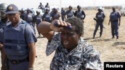 Uma mulher a chorar confronta os polícias que dispararam sobre os mineiros