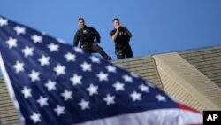 Agentes del Servicio Secreto vigilan desde la azotea de un edificio.