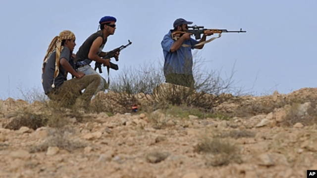 Libyan revolutionary fighters look for a target outside Sirte, Libya, Thursday, Sept. 29, 2011.