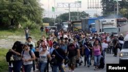 Yon gwo gwoup sitwayen Peyi Ondiras k ap kouri pou lamizè ak vyolans pran wout k ap mennen yo Ozetazini. Yo kite vil San Pedro Sula, nan pati nò Ondiras. (Foto: REUTERS/Jorge Cabrera, 13 oktòb 2018).