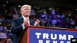 ຜູ້ລົງແຂ່ງຂັນເອົາຕຳແໜ່ງປະທານາທິບໍດີ ຈາກພັກຣີພັບບລີກັນ ທ່ານ Donald Trump ຕົບມືໃນລະຫວ່າງການໂຄສະນາຫາສຽງ ທີ່ມະຫາວິທະຍາໄລ ແຫ່ງລັດ North Carolina ທີ່ Wilmington, 9 ສິງຫາ, 2016.