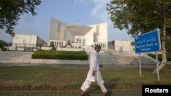 Seorang pria melintasi gedung Mahkamah Agung Pakistan di Islamabad (Foto: dok). MA Pakistan telah memanggil PM Raja Pervez Ashraf atas tuduhan tidak mengindahkan perintah MA untuk membuka kembali kasus korupsi yang dituduhkan atas Presiden Zardari.