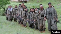 Kurdistan Workers Party (PKK) fighters walk on the way to their new base in northern Iraq May 14, 2013. The first group of Kurdish militants to withdraw from Turkey under a peace process entered northern Iraq on Tuesday, and were greeted by comrades from