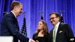 U.S. Trade Representative Robert Lighthizer, left, shakes hands with Mexico's Secretary of Economy Ildefonso Guajardo Villarreal, accompanied by Canadian Foreign Affairs Minister Chrystia Freeland, after attending a news conference at the start of NAFTA Renegotiations in Washington, Aug. 16, 2017.