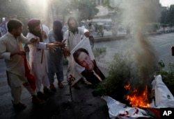 FILE - Supporters of Pakistani radical groups burn a poster of Pakistani Prime Minister Imran Khan during a rally to condemn a Supreme Court decision that acquitted Asia Bibi, a Christian woman, who spent eight years on death row accused of blasphemy, in