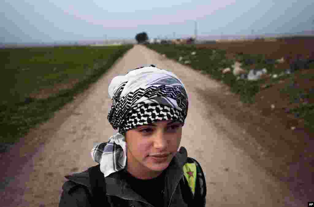 A member of the Popular Protection Units stands guard at a check point near Qamishli, Syria, March 3, 2013.