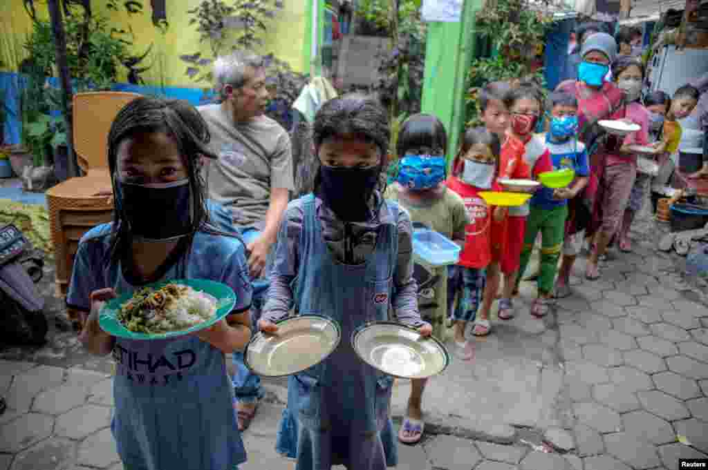Locals wearing protective masks carry plates while queueing for food distributed for free amid the spread of coronavirus disease (COVID-19) in Bandung, West Java province, Indonesia.