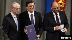 European Council President Herman Van Rompuy, European Commission President Jose Manuel Barroso, and European Parliament President Martin Schulz (L-R) are pictured with the Nobel diploma on the podium in Oslo City Hall during Nobel Peace Prize ceremony De
