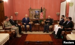 FILE - Afghanistan's President Ashraf Ghani, center right, and U.S. special envoy for peace in Afghanistan, Zalmay Khalilzad,center left, meet in Kabul, Nov.10, 2018.