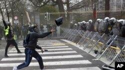 Un manifestante arroja un objeto a la fila de la policía durante una manifestación en Bruselas, el sábado 8 de diciembre. (Foto: AP)