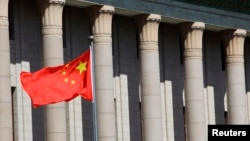 FILE- A Chinese national flag flaps in the wind outside the Great Hall of the People in Beijing.
