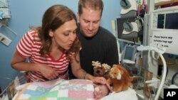 La congresista Jaime Herrera junto a su esposo Dan Beutler observan a la pequeña Abigail, quien está hospitalizada en California donde el equipo médico ha declarado estar optimista.
