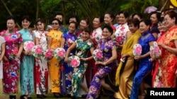 中国海南省琼海,国际妇女节前夕,旗袍秀中的妇女摆姿势拍照。(2018年3月7日)