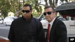 AC/DC drummer Phil Rudd, right, who pleaded guilty to a charge of threatening to kill a man who used to work for him, arrives at a court in Tauranga, New Zealand, April 21, 2015.