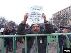 3月7日莫斯科反战集会,物理学家米哈伊尔手举标语:克里米亚属于乌克兰, 公民们(我们的)祖国处在危险之中,我们的坦克在别人的土地上(美国之音 白桦拍摄)