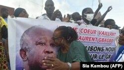 Une partisane de Laurent Gbagbo embrasse son portrait à Abidjan le 31 août 2020, lors du dépôt de son dossier de candidature à la commission électorale. (Photo by SIA KAMBOU / AFP)