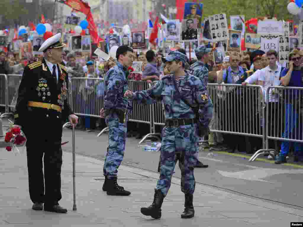 A member of Russia's National Guard presents flowers to a veteran during celebrations of Victory Day, which marks the anniversary of the victory over Nazi Germany, Moscow, May 9, 2019.