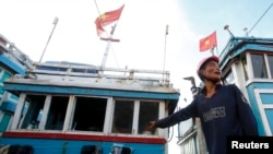 越南渔民手指他的渔船上损坏的窗户,他说他今年已经被中国船只骚扰20次了(2014年7月1日)