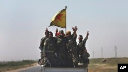 FILE - U.S.-backed Syrian Democratic Forces fighters stand on their pickup as the flash victory signs after battling the Islamic State militants, northeast Syria, July 26, 2017.