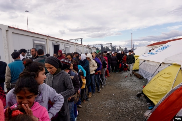 FILE - Refugees queue up for food, where they can wait in line for three or four hours, March 2016. (J. Dettmer/VOA)