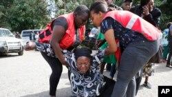 Wafanyakazi wa Red Cross wakimsaidia mwanamke ambaye alifikwa na majonzi baada ya kufahamu kuwa ndugu yake ameuwawa katika shambulizi la kigaidi, Jumatano, Jan. 16 2019, katika jengo la kuhifadhi maiti huko Chiromo Nairobi, Kenya.