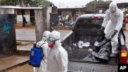 Các nhân viên y tế trong trang phục bảo hộ sau khi chuyển thi thể của một người mà họ nghi là chết vì nhiễm phải virus Ebola ở Monrovia, Liberia, 16/9/2014.