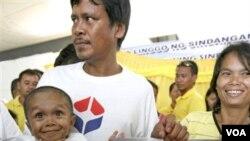 Junrey Balawing yang tepat berusia 18 tahun, didampingi kedua orang tuanya Reynaldo dan Concepcion Balawing, berpose dengan sertifikat Guinness World Records di kota Sindangan, Filipina selatan (12/6).