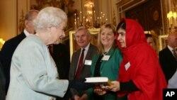 Malala Yousafzai, derecha, entrega una copia de su libro a la reina Elizabeth de Inglaterra durante una recepción en honor a la juventud celebrada en palacio.