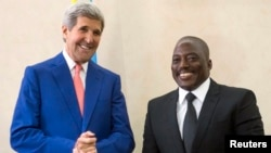President of the Democratic Republic of Congo (DRC) Joseph Kabila (R) welcomes U.S. Secretary of State John Kerry at the Palais de la Nation in Kinshasa, May 4, 2014.