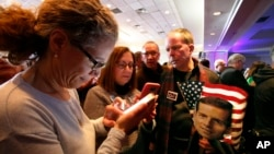People check election returns on their phones at the election night party for Conor Lamb, the Democratic candidate for the March 13 special election in Pennsylvania's 18th Congressional District, on Canonsburg, Pa., Tuesday, March 13, 2018. (AP Photo)