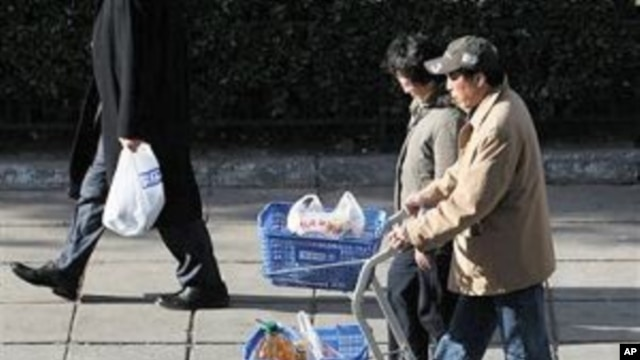 An elderly Chinese couple pushes carts load with groceries as they shop at a supermarket in Beijing, China, 11 Nov 2010