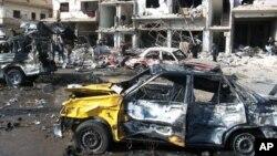 Ciudadanos sirios observan el lugar donde dos bombas explotaron en el barrio progubernamental de Zahraa, en Homs, Siria, el domingo, 21 de febrero de 2016.