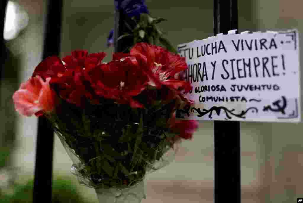 """Un ramo de flores para rendirle respeto a Fidel Castro con una pancarta en español """"Tu lucha vivirá ahora y siempre"""" se exhibe fuera de la embajada de Cuba en Buenos Aires, Argentina, el sábado 26 de noviembre de 2016."""