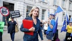 Anggota parlemen Inggris, Amber Rudd, melewati beberapa pengunjuk rasa anti-Brexit saat meninggalkan kantornya di London, 2 September 2019.