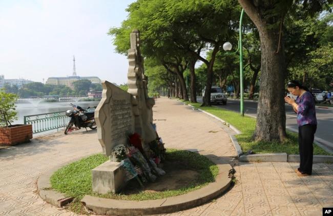Una mujer brinda sus respetos en el monumento al fallecido senador estadounidense John McCain en Hanoi, Vietnam, el lunes, 27 de agosto de 2018.