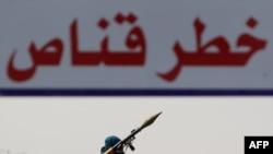 Phiến quân Libya trang bị với súng phóng lựu. Phía trên là biểu ngữ với dòng chữ 'Bắn tỉa, nguy hiểm' tại lối vào thành phố Ajdabiya, ngày 23/4/2011